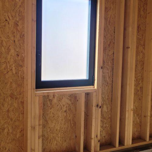 Fenêtre aluminium avec vitrage dépoli sur maison en ossature bois